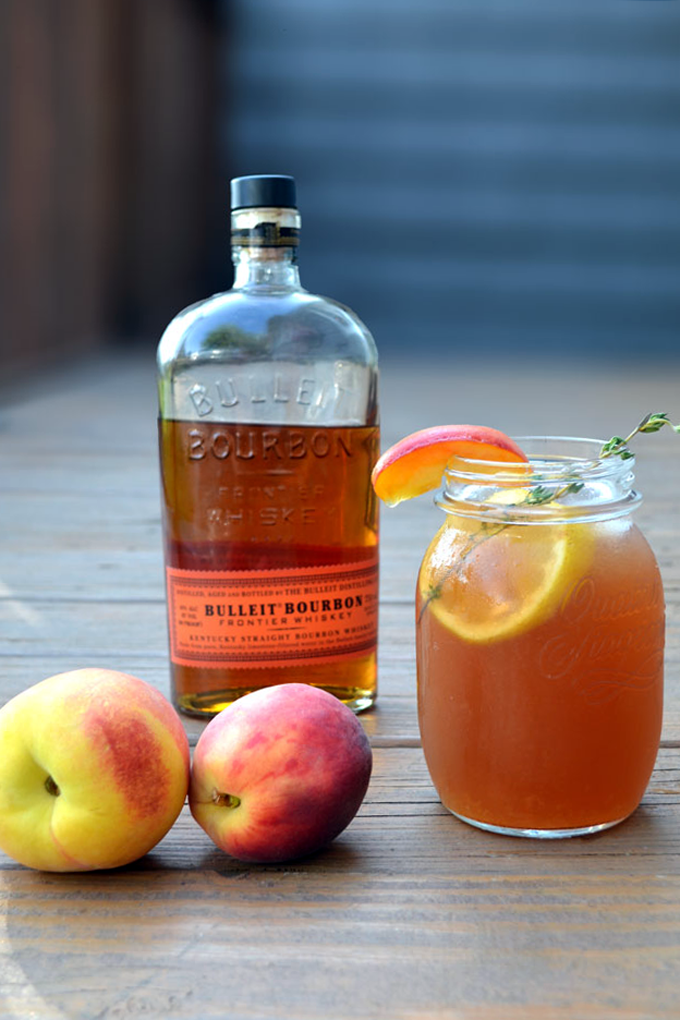 Bottle of burbon and mason jar with peach sweet tea
